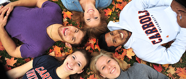 students in leaves smiling up at camera