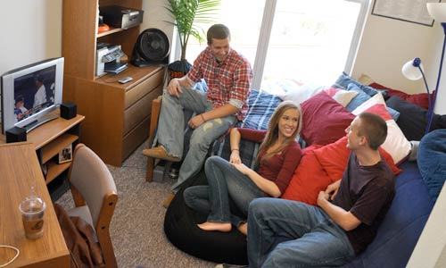 Photo of three students watching TV in dorm