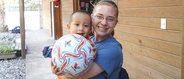 student and child with soccer ball