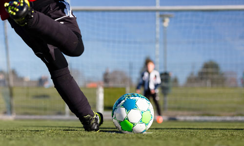 a foot kicking a soccer ball toward goal