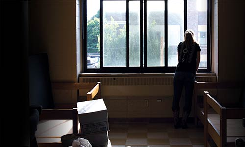 a student looking out of a residence hall window