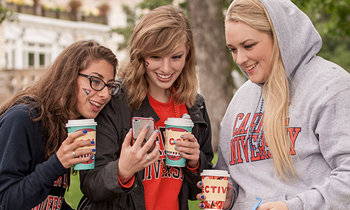 3 female students looking at phone with coffee