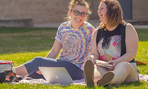 Two students sharing a laugh on Main Lawn while studying