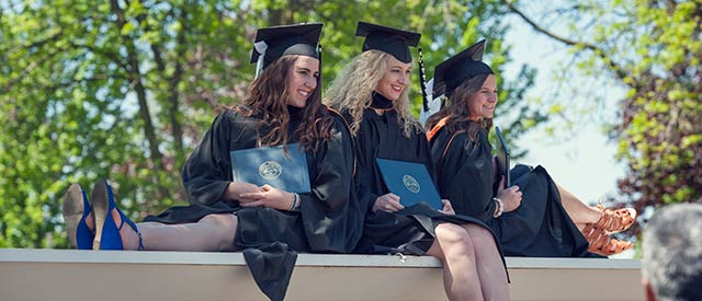 Three female students taking pictures after commencement